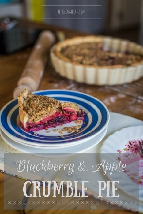 A rustic kitchen counter with Blackberry and Apple Crumble Pie, a rolling pin and an empty plate