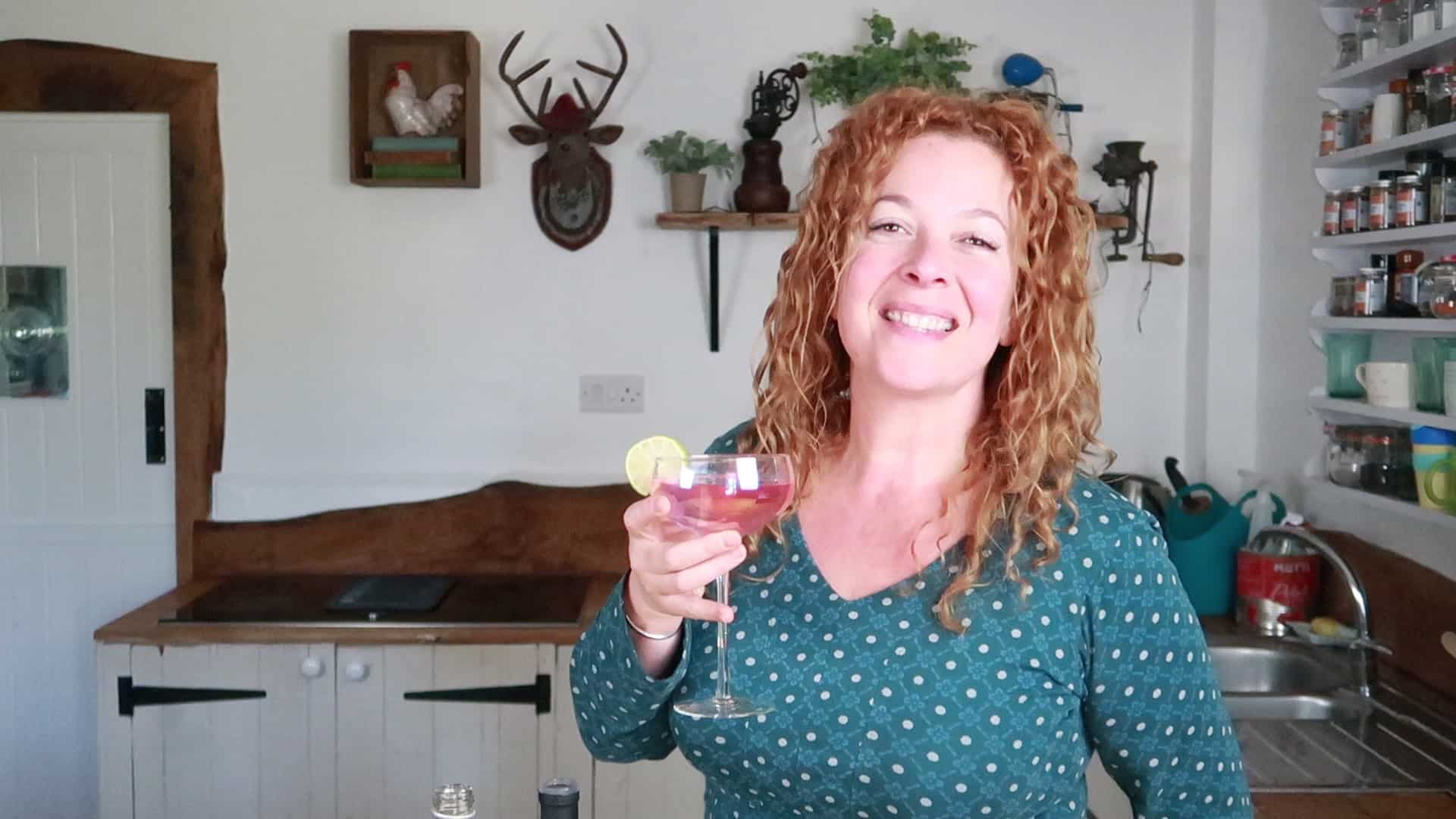 Woman holding glass of pink elephant cocktail, smiling at the camera