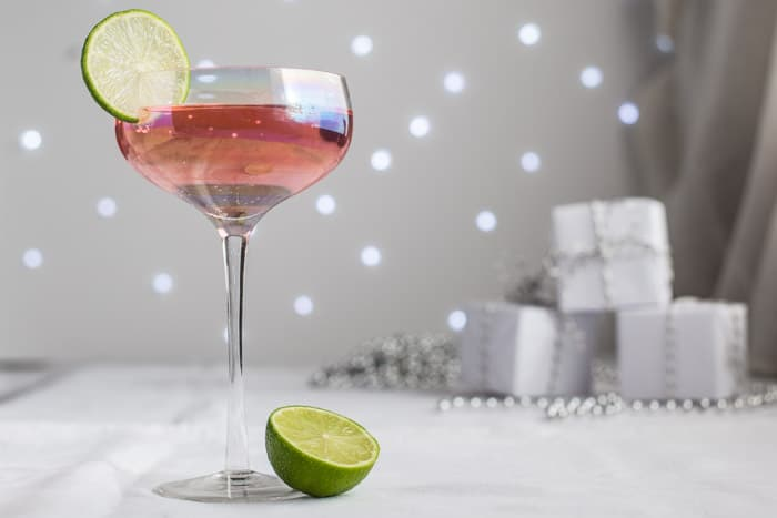 Glass of Pink Elephant Cocktail garnished with a slice of Lime and festive parcels on a grey and white background