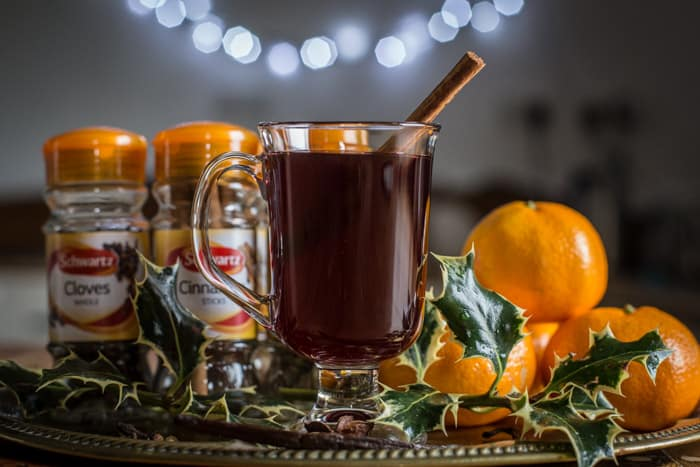 Glass of slow cooker mulled wine with satsumas, holly and spices