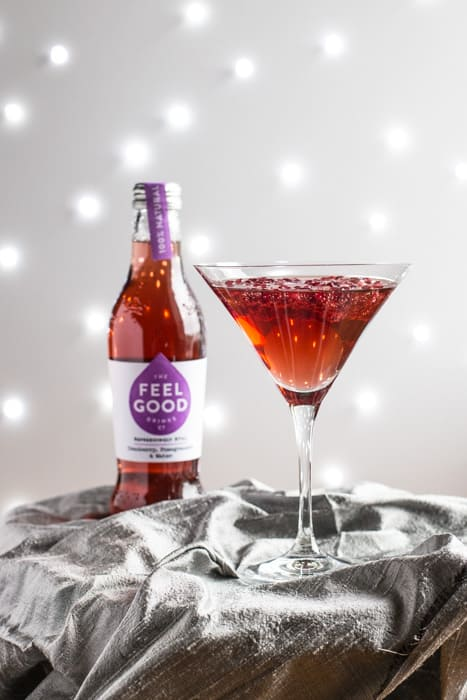 A cocktail glass of Pomagranate Popper Cocktail beside a bottle of Feel Good Cranberry and Pomagranate juice