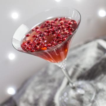 cocktail glass with pomegranate popper cocktail and pomegranate seeds against a sparkly grey background