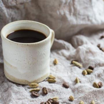 Small white mug of Cardamom Coffee, surrounded with cardamom pods