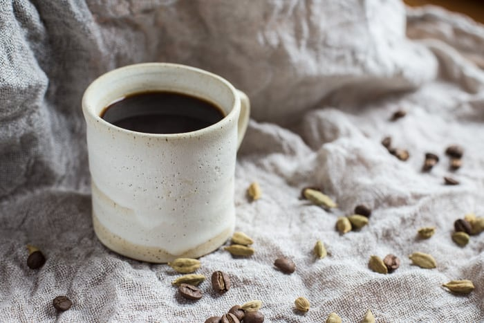 Cardamom Coffee in a mug with scattered coffee beans