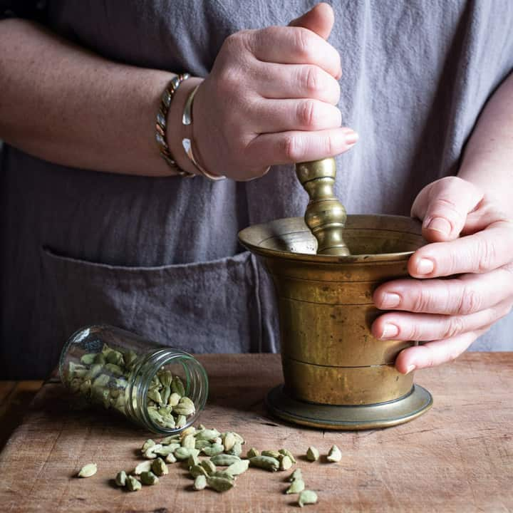 womans hands smashing green cardamom seeds in a brass pestle and mortar to make cardamom coffee