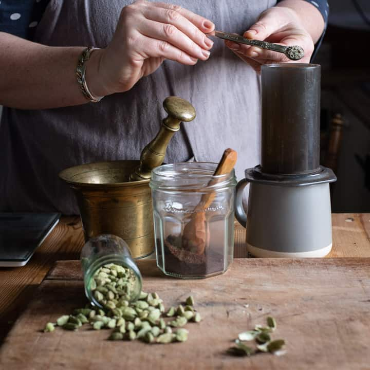womans hands tipping freshly ground cardamom seeds into an Aeropress coffee maker