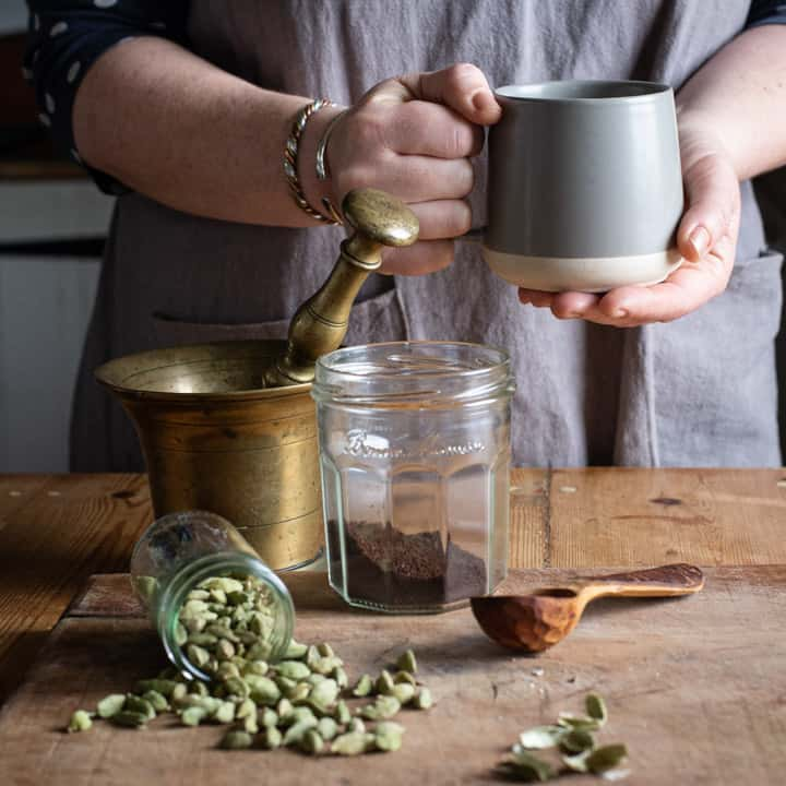 womands hands holding a grey mug of hot cardamom coffee over a messy scene of cardamom pods and coffee making paraphenalia