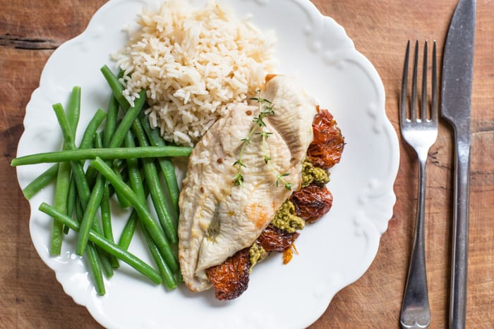 Sundried Tomato and Pesto Stuffed Chicken Breast on a white plate with basmati rice and green beans