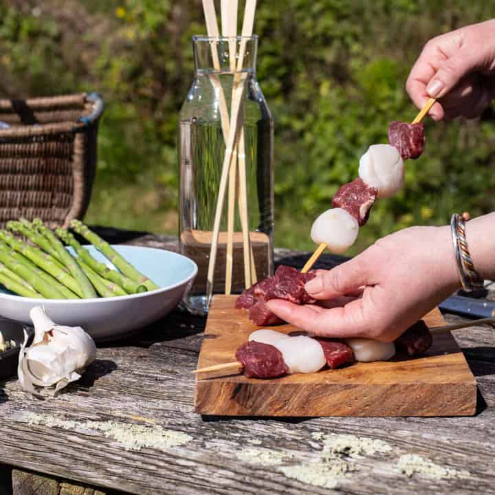 womans hands threading steak and scallops into wooden skewers in a rustic garden setting