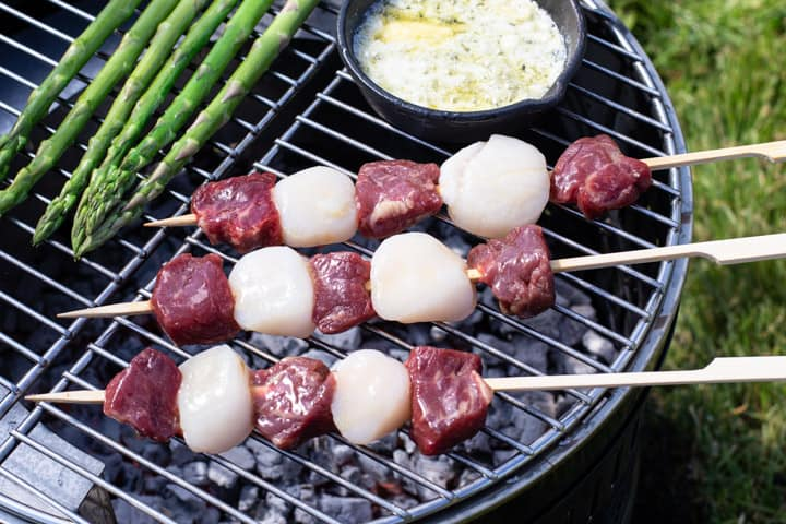 3 sirloins steak and scallop kebabs cooking on a garden BBQ with asparagus spears and garlic butter cooking in small cast iron pan