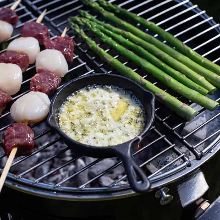 small black cast iron skillet filled with bubbling garlic butter on top of a BBQ with surf and turf kebabs and fresh asparagus spears