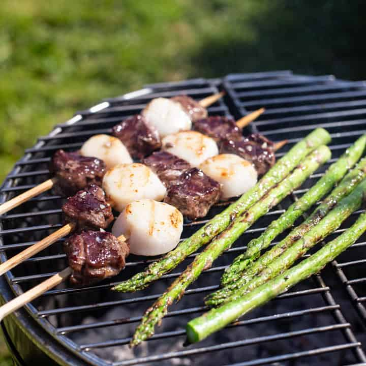 3 surf n turf kebabs cooking with asparagus on a silver and black grill with green grass in the background