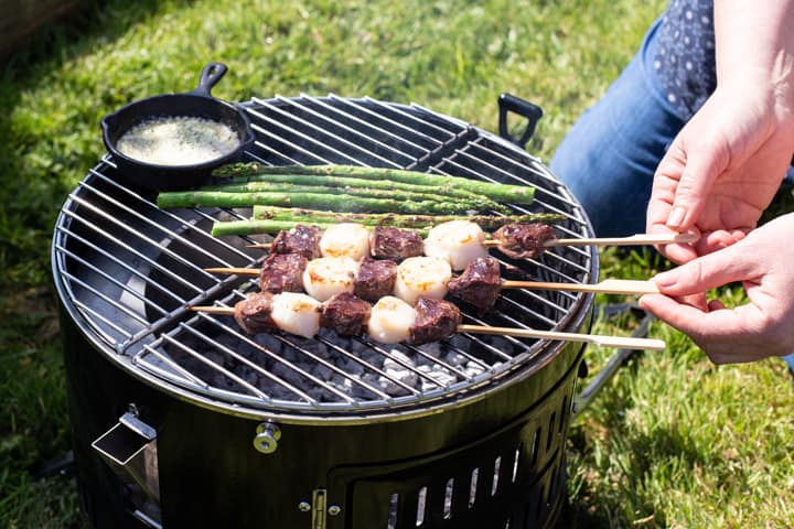 womans hands turning over surf and turf skewers on a BBQ grill with asparagus and a pot of garlic butter