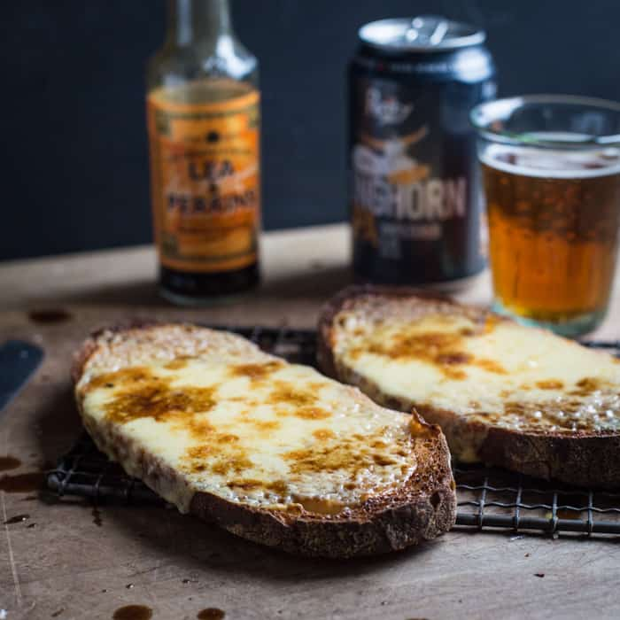 Cheese on toast, glass of beer and bottle of Worcester sauce
