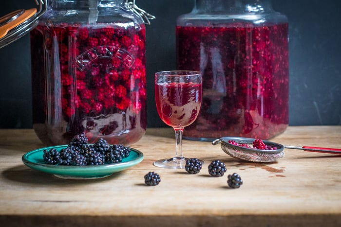 Blackberry Flavoured Vodka in a small wine glass and 2 kilner jars with a dish and a sieve both containing blackberrys