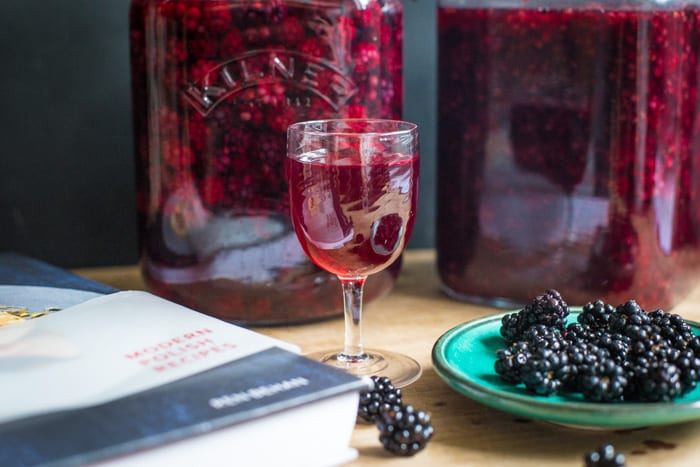 Blackberry Flavoured Vodka in a samall wine glass with 2 kilner jars a dish of blackberrys and a recipe book
