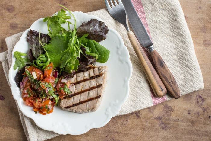 White plate with griddled tuna and salad, a white napkin and knife and fork