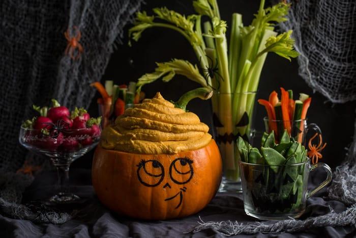 Cute Halloween pumpkin head overflowing with pumpkin dip, surrounded by vegetable crudites