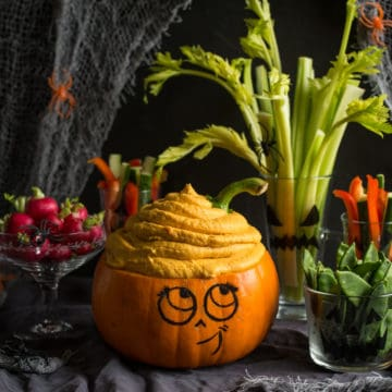 Cute smiling Halloween pumpkin with colourful vegetable crudites and pumpkin dip 'brains'!