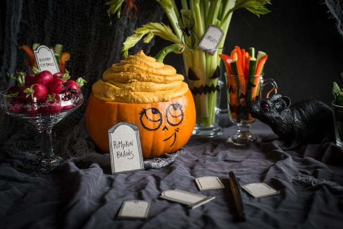 Healthy Halloween recipes includes dip labelled pumpkin brains, served in a scooped out pumpkin with a smiley face drawn onto it and crudites in glasses around it
