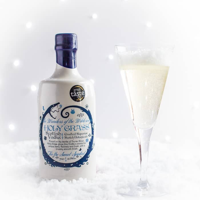 A bottle of Holy Grass Vodka and an Arctic Kiss vodka cocktail in a champagne flute