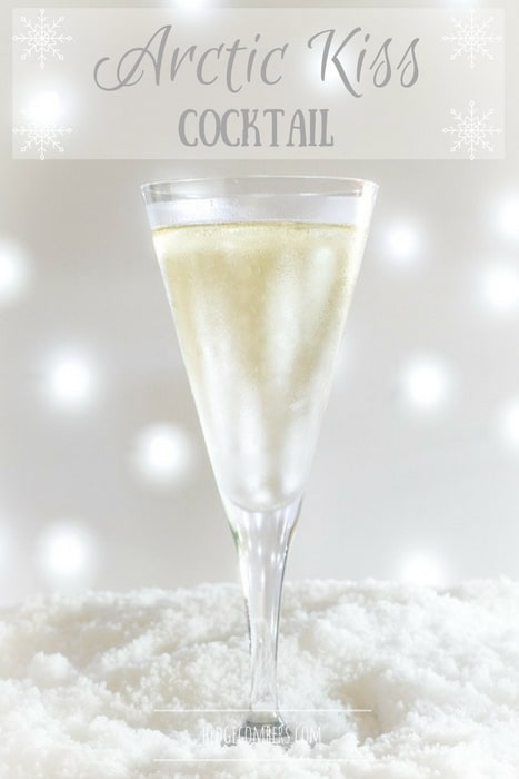 Champagne flute with light coloured cocktail on a bed of snow with bokeh background
