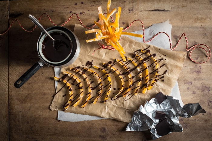 Freshly made Candied Orange Peel being drizzled with melted dark chocolate