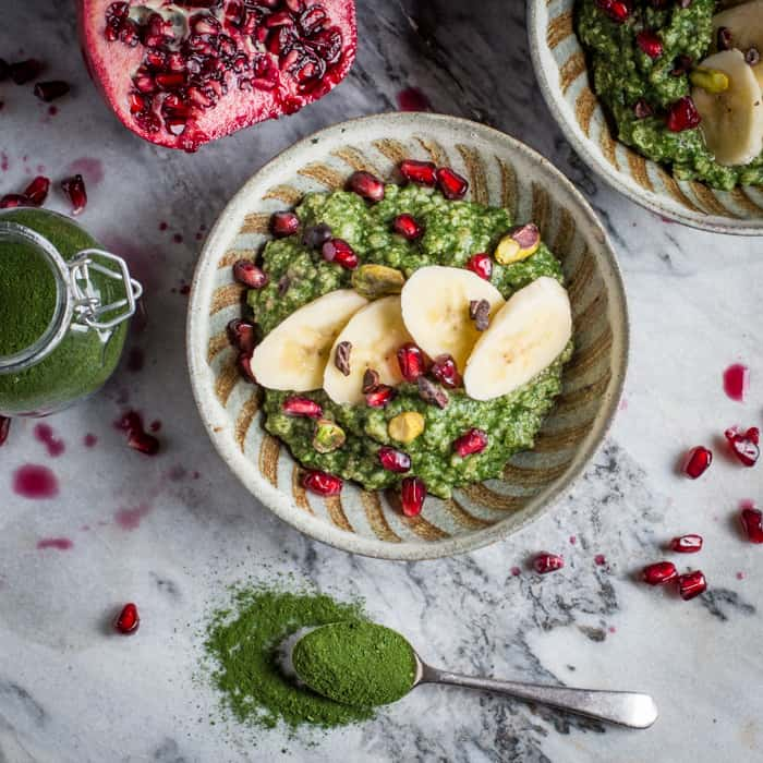 Bowl of pretty, bright green porridge made with DIY Green Superfood Powder, pomegranates, pistachios and banana