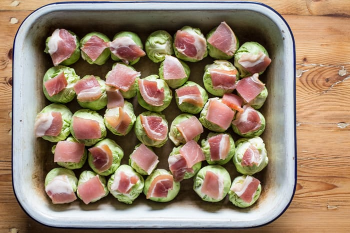 smashed Roast Sprouts with Bacon and Chestnuts in a roasting dish ready to cook