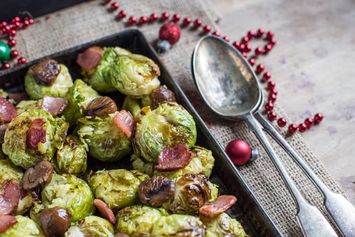 Smashed Sprouts with Bacon and Chestnuts in a roasting tin with a seving spoon beside them and Christmas decorations on the table