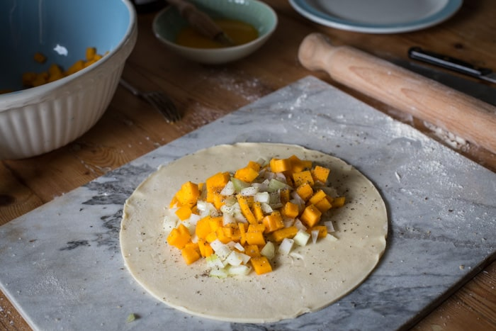a disk of shortcrust pastry with the raw butternut and sage filling, ready to be crimped and baked