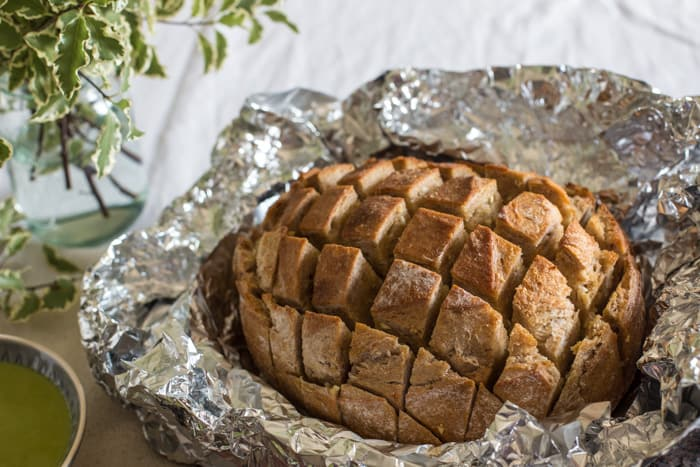 A loaf of sourdough bread, cut in a crisscross style and baked with garlic butter spread in between - YUM!