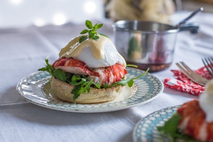 Lobster Eggs Benedict on china plates with christmas decorations