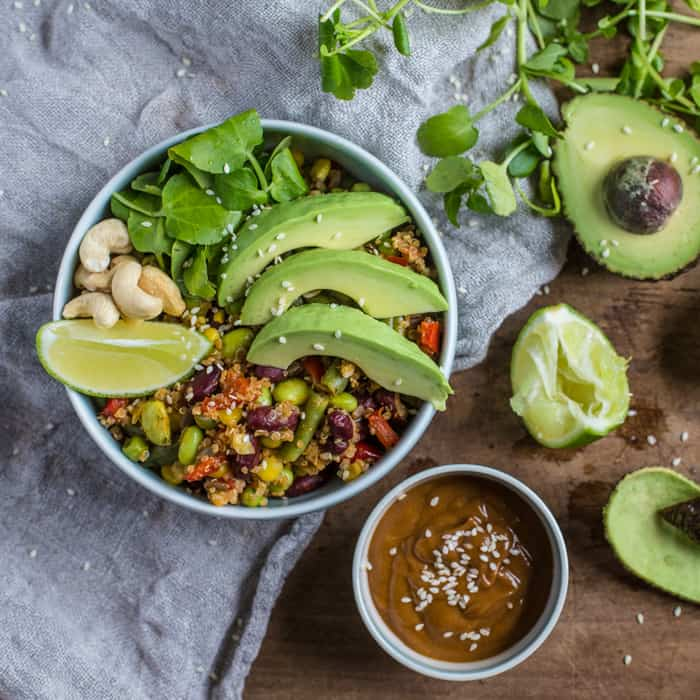 healthy nourish bowl with quinoa salad, avocado, peanut sauce and lime wedge