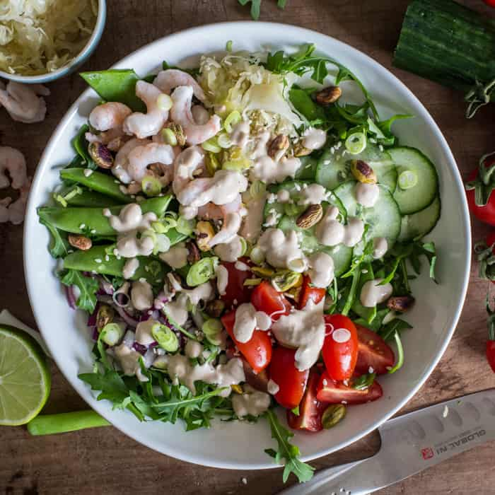 Small glass bottle of tahini sauce surrounded by a vibrant mix of salad vegetables, sauerkraut and olives