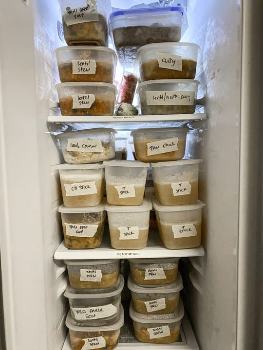 inside of a kitchen freezer with multiple plastic tubs full of nourishing homemade meals marked with masking tape and sharpie labels