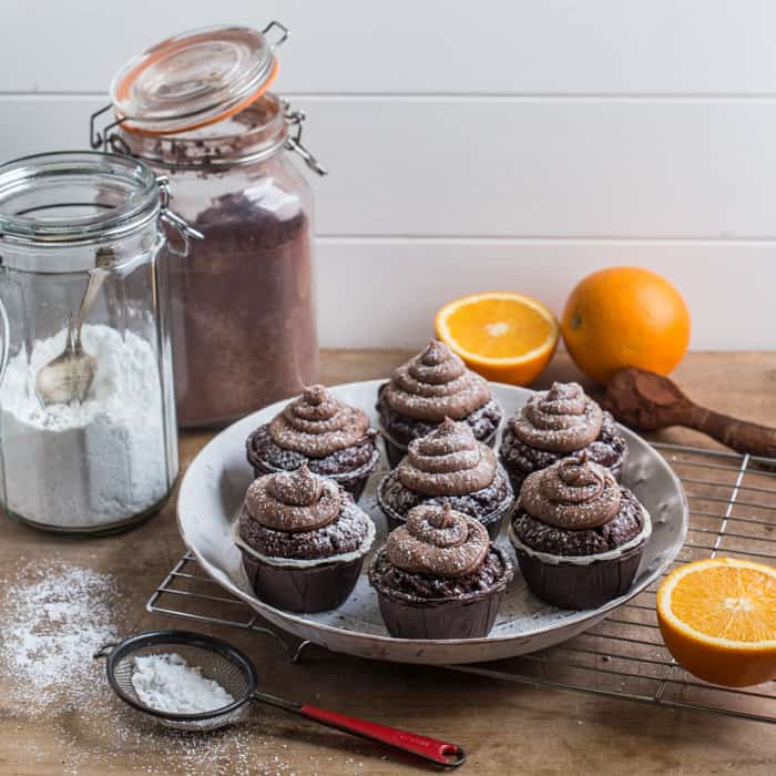 white plate with muffins and swirls of chocolate orange buttercream frosting, with jars of ingredients behind