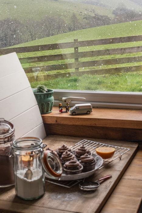 Mini photo studio next to window where muffins and swirls of chocolate orange buttercream frosting are being shot
