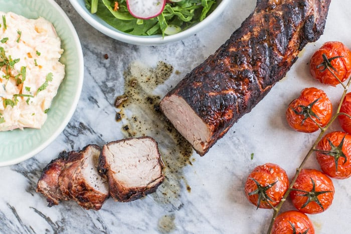 Juicy bbq pork tenderloin sliced on marble slab with bowls of salad and roast tomatoes