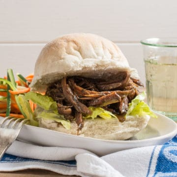 White bap stuffed with lettuce and juicy pulled lamb. on a white plate with salad and a small glass of wine in the background.