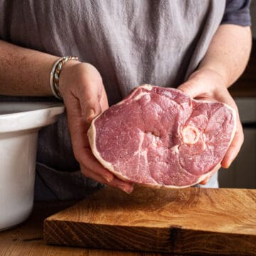 womans hands holding joint of lamb ready to go in slow cooker