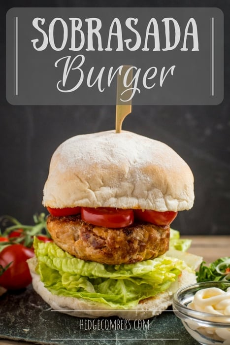 A tall sobrasada burger layered with lettuce, tomato and a wooden skewer holding it all together