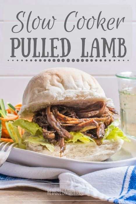 White bap stuffed with lettuce and juicy slow cooker pulled lamb. on a white plate with salad and a small glass of wine in the background.