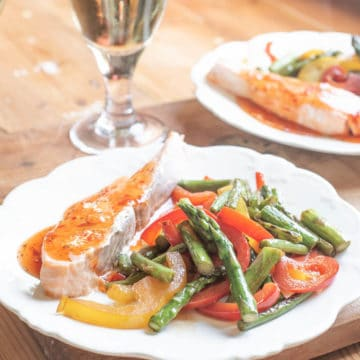 White plate with salmon fillet and asparagus stir fry