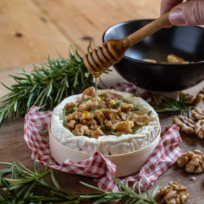Molten BBQ baked Camembert cheese melting out of its wooden tub with rosemary and walnuts being drizzled with honey all on a wooden board