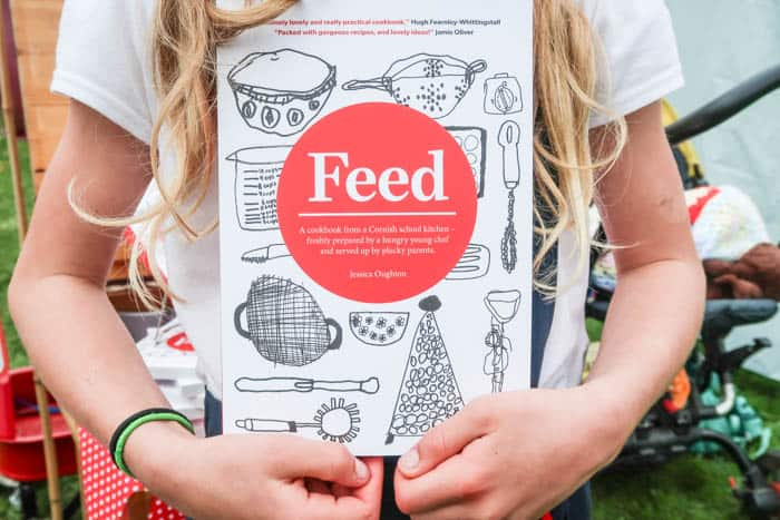 Young girl holding a book called Feed