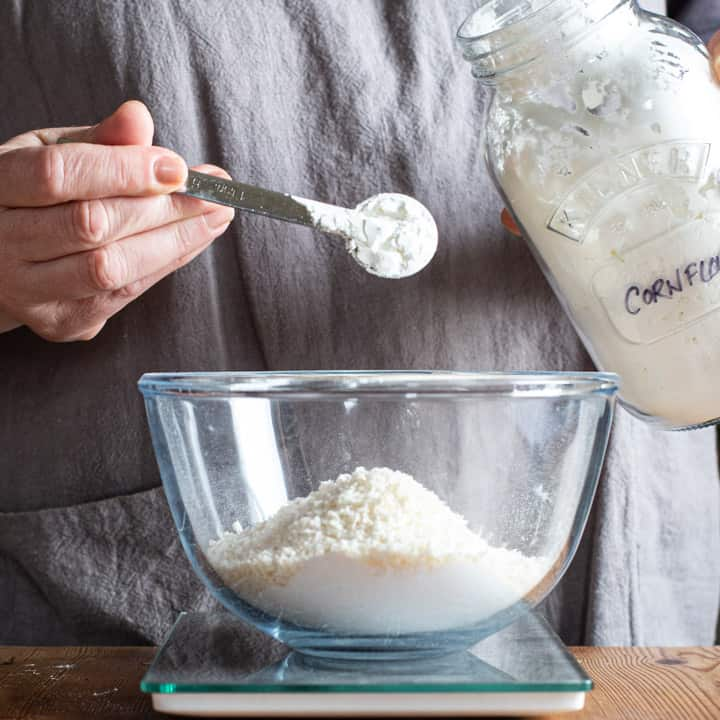 womans hand tipping cornflour from a silver spoon into a glass mixing bowl