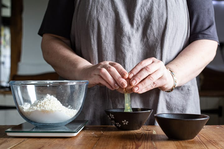 womans hands cracking an egg into a small black bowl on a wooden kitchen counter