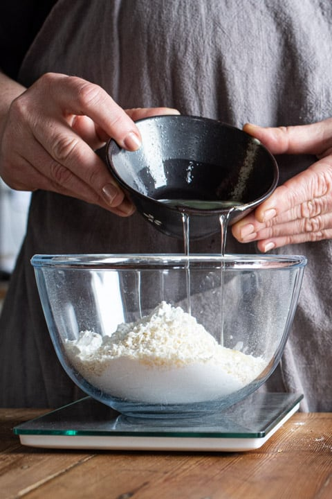womans hands pouring an egg white from a small black bowl into a larger glass bowl filled with white baking ingredients