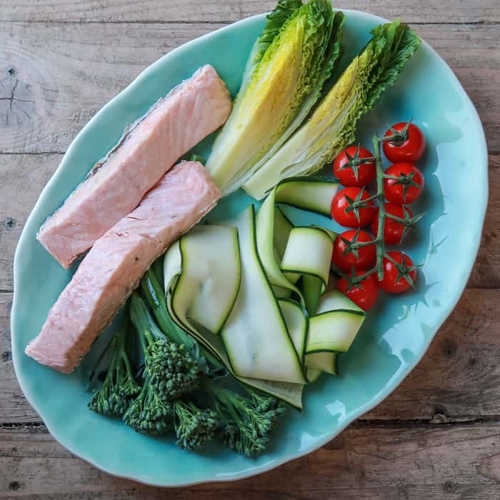 turquoise plate with grilled lettuce, cherry tomatoes, broccoli and 2 pieces of steamed salmon with green dressing